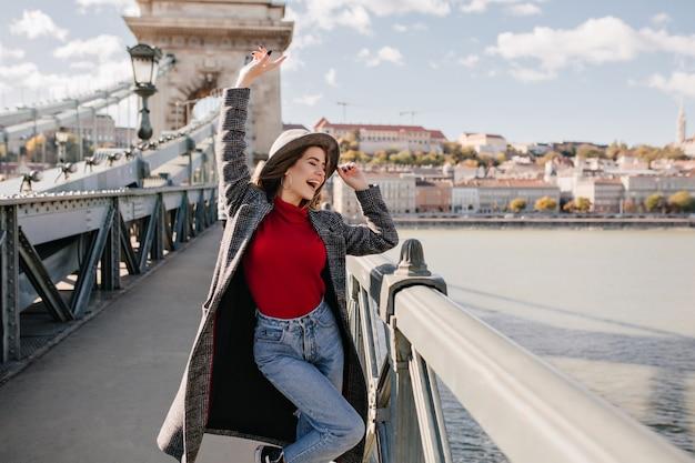 Mooie jonge vrouw in blauwe spijkerbroek en lange jas dansen op de brug in de buurt van triomfboog