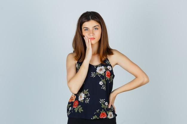 Mooie jonge vrouw in blouse die lijdt aan pijnlijke kiespijn