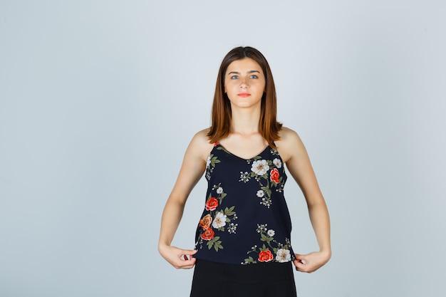 Mooie jonge vrouw in blouse, rok die haar blouse naar beneden trekt en er zelfverzekerd uitziet