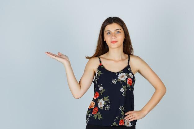 Mooie jonge vrouw in blouse verwelkomend gebaar tonen en zelfverzekerd kijken