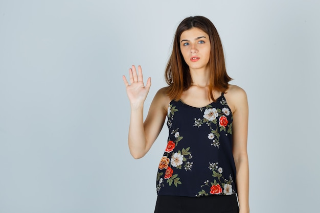 Mooie jonge vrouw in blouse zwaaiende hand voor groet en op zoek zelfverzekerd