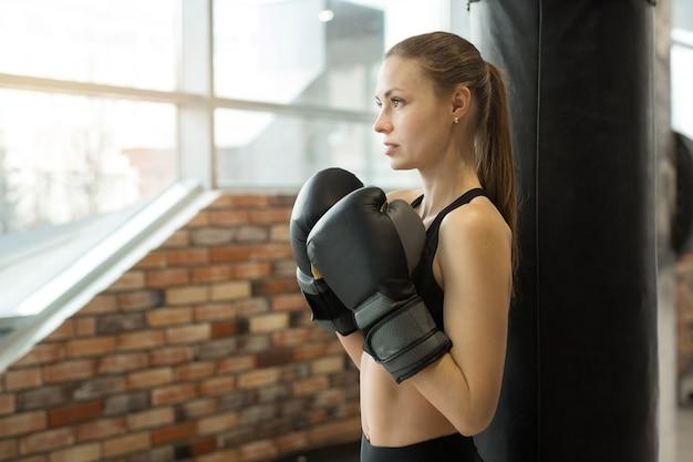 Mooie jonge vrouw in bokshandschoenen op training