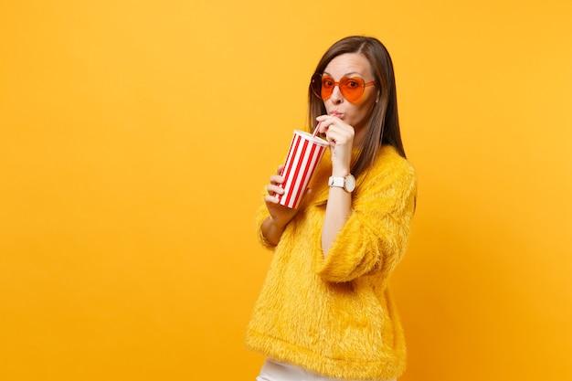 Mooie jonge vrouw in bont trui en hart oranje bril drinken cola of frisdrank uit plastic beker geïsoleerd op heldere gele achtergrond. mensen oprechte emoties, lifestyle concept. reclame gebied.