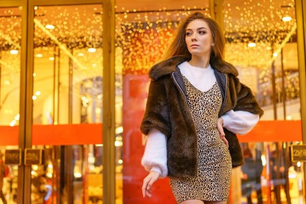 Mooie jonge vrouw in bontjas die zich naast de winkel bevindt