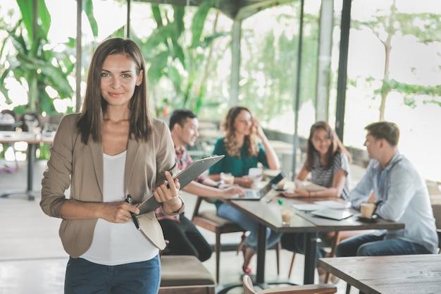 Mooie jonge vrouw in café creatieve ontmoeting met haar team