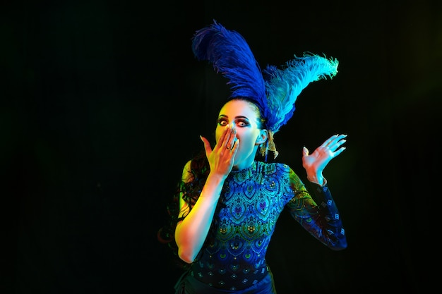 Mooie jonge vrouw in carnaval en maskeradekostuum in kleurrijke neonlichten op zwarte muur