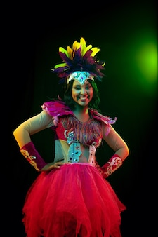 Mooie jonge vrouw in carnaval-masker en maskeradekostuum in kleurrijke lichten