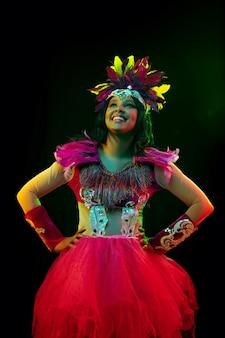 Mooie jonge vrouw in carnaval-masker en maskeradekostuum in kleurrijke lichten Gratis Foto