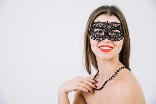 Mooie jonge vrouw in carnaval-masker en op witte achtergrond