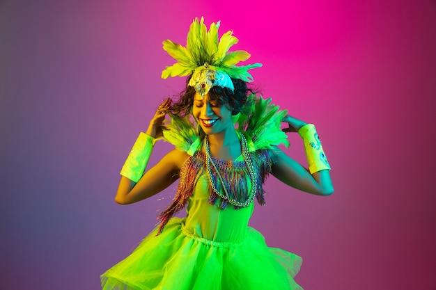 Mooie jonge vrouw in carnaval, stijlvol maskeradekostuum met veren die op gradiëntachtergrond dansen in neon.