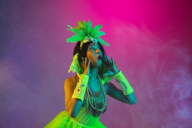 Mooie jonge vrouw in carnaval, stijlvol maskeradekostuum met veren die op gradiëntmuur dansen in neon