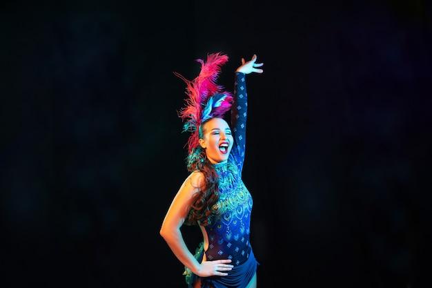 Mooie jonge vrouw in carnaval, stijlvol maskeradekostuum met veren op zwarte achtergrond in neonlicht.