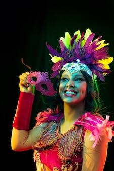 Mooie jonge vrouw in carnavalsmasker en maskeradekostuum in kleurrijke lichten