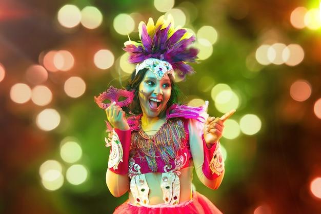 Mooie jonge vrouw in carnavalsmasker en stijlvol maskeradekostuum met veren en sterretjes in kleurrijke bokeh op zwarte achtergrond