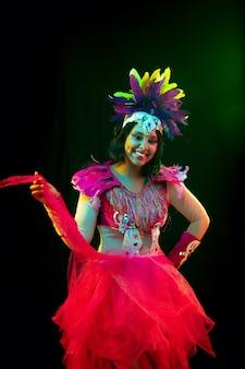 Mooie jonge vrouw in carnavalsmasker en stijlvol maskeradekostuum met veren in kleurrijke lichten en gloed op zwarte achtergrond
