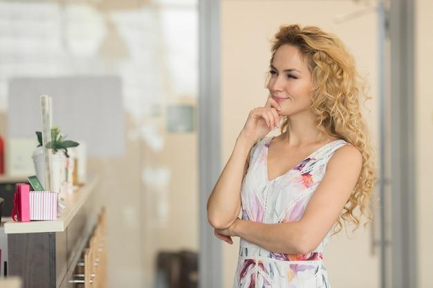 Mooie jonge vrouw in comfortabel café gaat een bestelling plaatsen.