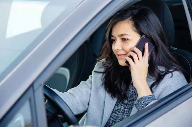 Mooie jonge vrouw in de auto die en op een celtelefoon glimlacht spreekt.