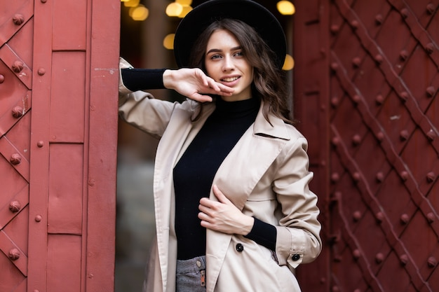 Mooie jonge vrouw in de buurt van ouderwetse deur met zwarte hoed en jas op straat.