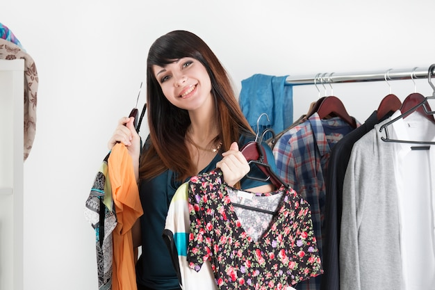 Mooie jonge vrouw in de buurt van rek met kleren chioce met verschillende jurken in haar handen maken