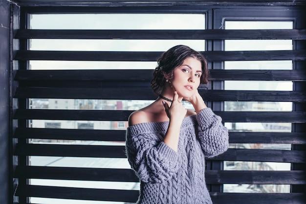Mooie jonge vrouw in de grijze trui bij het raam in de winter, zachtaardig en attent