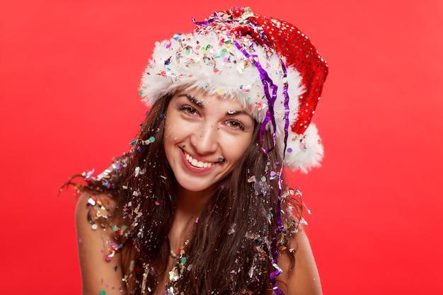 Mooie jonge vrouw in de hoed van de kerstman het glimlachen. kerstverhaal. ansichtkaart. verticaal. rood