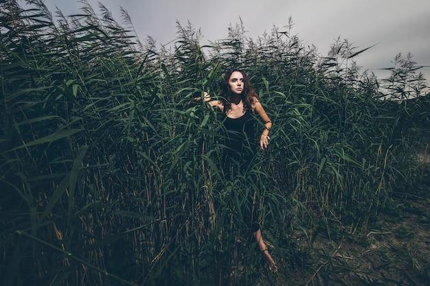 Mooie jonge vrouw in de jungle in gras kreupelhout in zwarte jurk