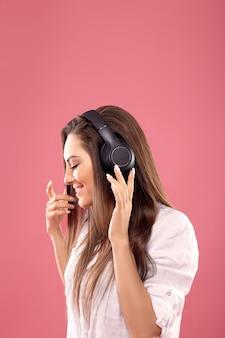 Mooie jonge vrouw in draadloze koptelefoon luisteren naar muziek en dansen