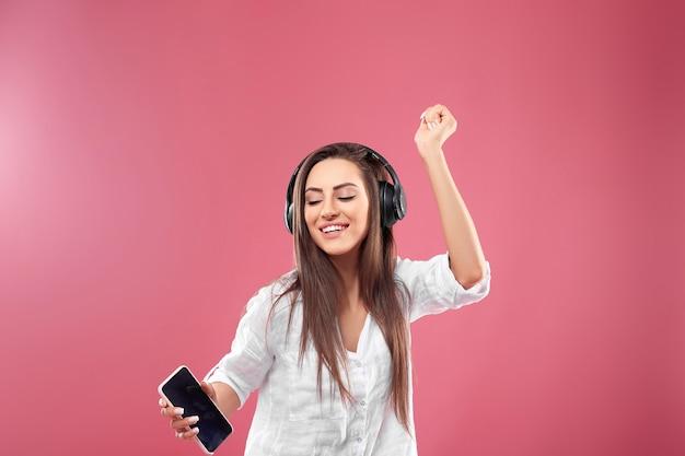 Mooie jonge vrouw in draadloze koptelefoon luisteren naar muziek met behulp van mobiel