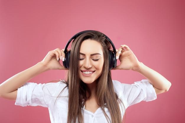 Mooie jonge vrouw in draadloze koptelefoon luisteren naar muziek
