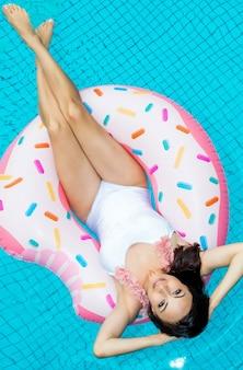 Mooie jonge vrouw in een badpak ontspannen op opblaasbare donut in zwembad.