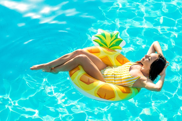 Mooie jonge vrouw in een badpak ontspannen op opblaasbare rubberen ringvormige gele ananas in zwembad. genieten van de zomer. vakantie stemming.
