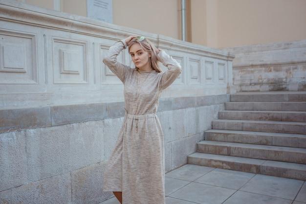 Mooie jonge vrouw in een beige gebreide jurk loopt door de straten van moskou, zonnig lenteweer