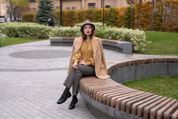 Mooie jonge vrouw in een beige herfstjas en zonnebril zit op een bankje op een bloembed te wachten op h...