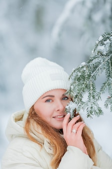 Mooie jonge vrouw in een besneeuwd bos. vuren takken in de sneeuw. mooie winter. winter bos.