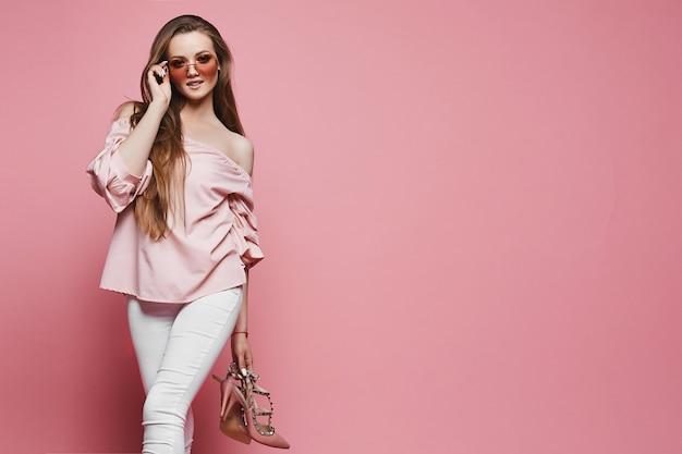 Mooie jonge vrouw in een blouse met naakte schouders en modieuze zonnebril die modieuze schoenen in hand houden en bij roze geïsoleerde achtergrond stellen ,. kopieer ruimte aan de rechterkant voor reclame