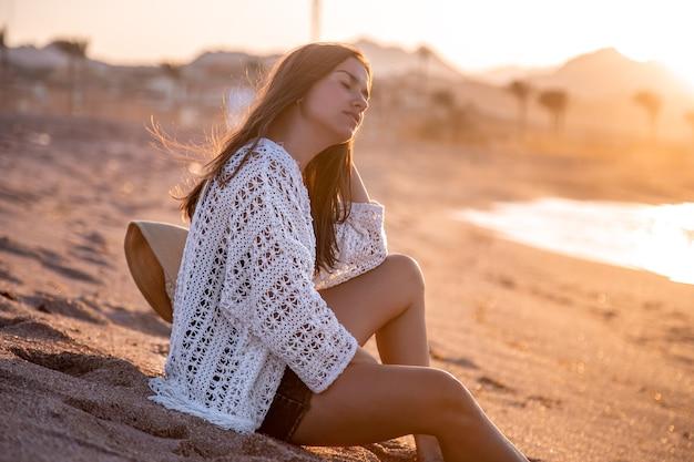 Mooie jonge vrouw in een boho-stijl cape zit op het strand bij zonsondergang.