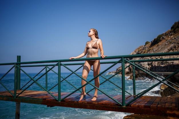 Mooie jonge vrouw in een bruin zwempak loopt op de pier aan het strand aan zee op een zonnige zomerdag Premium Foto