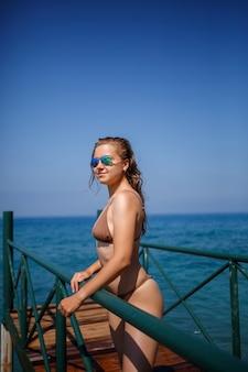 Mooie jonge vrouw in een bruin zwempak loopt op de pier aan het strand aan zee op een zonnige zomerdag
