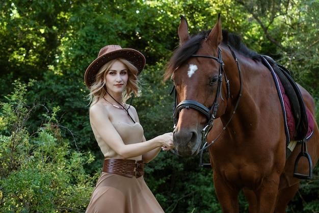 Mooie jonge vrouw in een cowboyhoed in de buurt van een paard op de natuur in het park