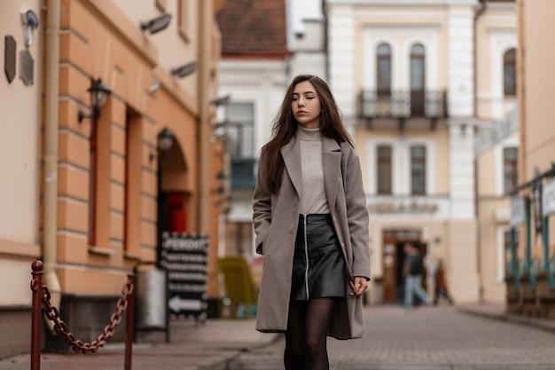 Mooie jonge vrouw in een elegante jas met een stijlvolle zwarte handtas staat op een straat in de stad