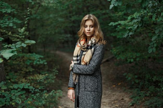 Mooie jonge vrouw in een gebreide sjaal en herfstjas in de buurt van de groene bladeren