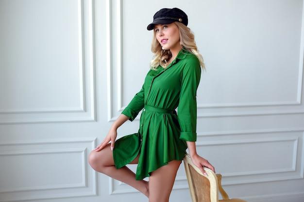 Mooie jonge vrouw in een groene korte jurk poseren in een witte kamer. mode, schoonheid, glamour concept.