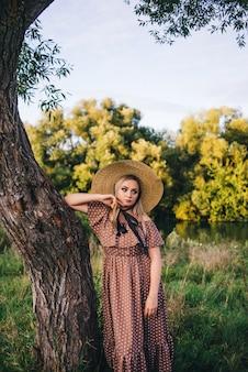 Mooie jonge vrouw in een hoed en jurk wandelingen in de natuur in de herfst.