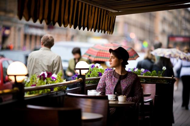 Mooie jonge vrouw in een hoed met een kopje thee zitten in een cafe, kijkend naar mensen aan het passeren