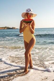 Mooie jonge vrouw in een hoed met watermeloen