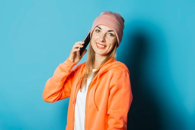 Mooie jonge vrouw in een hoodie en een hoed met een glimlach houdt een mobiele telefoon