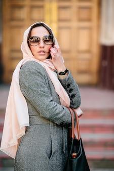 Mooie jonge vrouw in een jas met een tas poseren