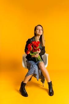 Mooie jonge vrouw in een jurk en een zwart leren jasje zit op een stoel met rode tulpen op een gele muur