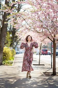 Mooie jonge vrouw in een jurk in bloeiende sakurabomen. het is een warme lentedag buiten