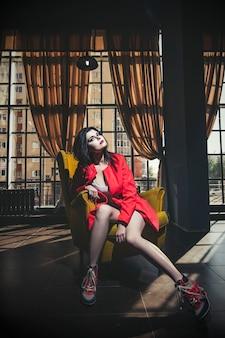 Mooie jonge vrouw in een koraal jas en sneakers zit op een gele stoel, kleurrijk
